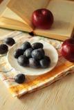 Pflaumen auf einer Platte und Äpfel mit hölzernem Hintergrund Stockfoto