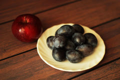 Pflaumen auf einer Platte und einem Apfel mit hölzernem Hintergrund Stockfotos