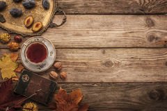 Pflaumen, Nüsse und Blätter mit Weinlesenotizbuch und Tee mit Filmfilter bewirken Hintergrund Stockbild
