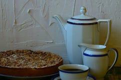 Pflaumenkrümeltörtchen mit Tasse Kaffee-, Rahmtopf- und Kaffeetopf auf weißem Hintergrund Stockbild
