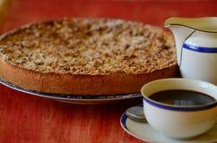 Pflaumenkrümeltörtchen mit Tasse Kaffee und Rahmtopf auf rotem Hintergrund Stockfoto