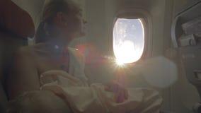 Pflegebaby der Frau während des Fluges, Ansicht gegen Sonnenaufflackern stock video footage