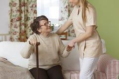 Pflegekraft, die älterer Frau hilft lizenzfreie stockbilder