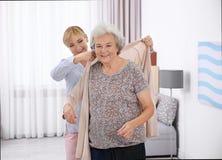 Pflegekraft, die älterer Frau hilft, Wolljacke an zu setzen stockfotos