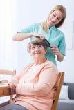 Pflegekraft, die das Haar der älteren Frau tut stockbild