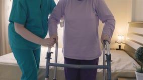 Pflegekraft, die dem älterem Frauenaufstehen und -weg mit einem Wanderer hilft stock video footage