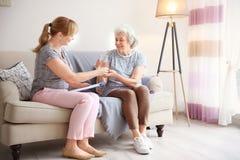 Pflegekraft, die der älteren Frau Glas Wasser gibt lizenzfreie stockbilder