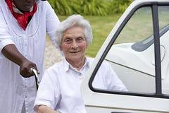 Pflegekraft, die einer behinderten Dame hilft, in das Auto zu kommen lizenzfreie stockfotografie