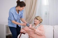 Pflegekraft, die für ältere Dame sich interessiert Lizenzfreie Stockfotos