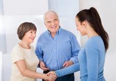 Pflegekraft, die Hände mit älteren Paaren rüttelt Lizenzfreies Stockfoto