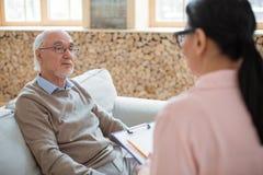 Pflegekraft, die Kontakt mit nachdenklichem älterem Mann aufnimmt lizenzfreie stockfotografie