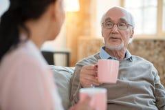 Pflegekraft und reizend älterer Mann, die Erfahrung austauschen stockfotos