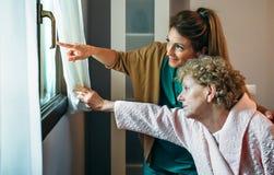 Pflegekraft, welche dem älteren Patienten die Ansicht durch das Fenster zeigt stockfoto