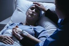 Pflegekraft, welche die kranke Frau mit Krebs sterbend im hospita stützt lizenzfreie stockfotografie