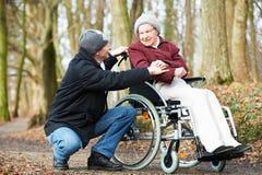 Pflegekraftmann, der mit behinderter älterer Frau am Rollstuhl in der Natur geht Stockfotos