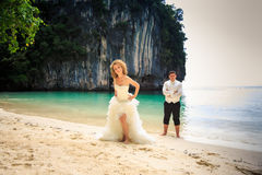 pflegen Sie blonde gelockte Braut im flaumigen Kleiderstand nah auf Strand Lizenzfreie Stockfotos