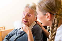 Pflegen Sie das Abwischen des Munds der älteren Frau im Pflegeheim Stockbild