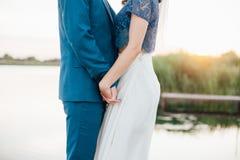 Pflegen Sie das Halten Braut ` s von Hand auf dem Sonnenuntergang Bräutigam und Braut Coupé von Liebhabern Ehemann- und Frauhändc Lizenzfreies Stockbild