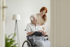 Pflegen Sie das Kümmern von  um einem Mann in einem Rollstuhl in einem Pflegeheim lizenzfreie stockbilder