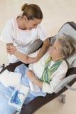 Pflegen Sie das Kümmern von  um älterer Frau im Ruhesitz Lizenzfreies Stockbild
