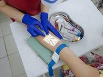 Pflegen Sie das Nehmen des Bluts für Analyse über Aderprojektorgerät Stockfoto