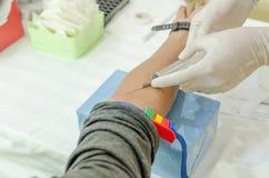 Pflegen Sie das Sammeln des Bluts vom Patienten für Analyse auf dem jährlichen h Lizenzfreies Stockfoto