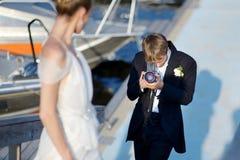 Pflegen Sie das Schießen seiner Braut mit einer alten Kamera Stockfotos