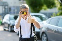 Pflegen Sie das Schießen seiner Braut mit einer sofortigen Kamera Stockfotos