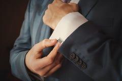 Pflegen Sie das Setzen auf Manschettenknöpfe, wie er angekleidet erhält Lizenzfreies Stockfoto