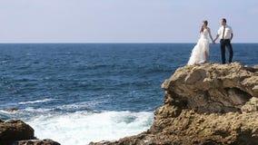 Pflegen Sie die Braut, die auf einem Felsen steht und küssen stock footage