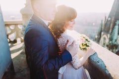 Pflegen Sie die Umfassung seiner reizend Frau am sonnigen Tag auf Balkon der antiken gotischen Kathedrale Stockfotos