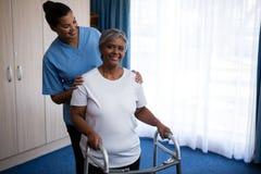 Pflegen Sie die Unterstützung der Frau beim Gehen mit Wanderer am Pflegeheim stockfotos
