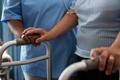 Pflegen Sie die Unterstützung des älteren Patienten beim Gehen mit Wanderer am Pflegeheim stockbilder