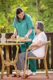 Pflegen Sie dienendes gesundes Frühstück zur glücklichen älteren Frau Stockbild