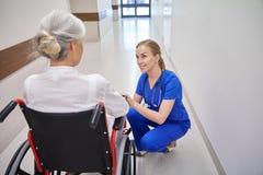Pflegen Sie mit älterer Frau im Rollstuhl am Krankenhaus Lizenzfreie Stockfotografie