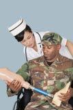 Pflegen Sie mit Soldaten US Marine Corps, der künstliches Glied hält, wie er im Rollstuhl über hellblauem Hintergrund sitzt lizenzfreie stockfotografie
