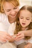 Pflegenthema - Frau schneidet Nägel der kleinen Mädchen stockbilder