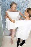 Pfleger oder Krankenschwester, die ältere Frau für Dusche unterstützen stockbilder