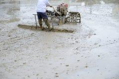 Pflugmaschine und -landwirt im ricefield Lizenzfreie Stockfotos