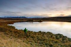 Pgotographer che lavora in un bello paesaggio in Islanda Fotografie Stock