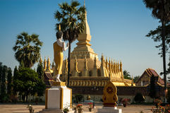 Pha That Luang. Wat That Luang Neua looking over to the national monument and Buddhist religious structure Pha That Luang was ereceted from 1566 on the site of a Royalty Free Stock Photo