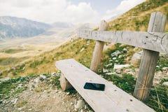 Phablet smartphone på den wood bänken i berg Royaltyfri Foto
