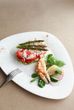 Phalanx crab with salad, lemon and asparagus. On a white plate with a fork in the frame. The Fund kraft paper Stock Image