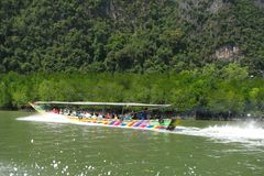 A bright long boat with tourists is floating on the water among mangroves surrounded by splashes. Side view stock images