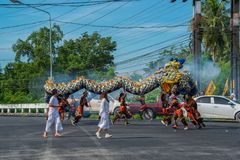 Phang Nga, Thailand - October 15, 2018: Group of men performing dragon dance on street marching in vegetarian festival parade in royalty free stock image