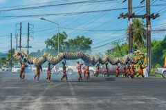 Phang Nga, Thailand - October 15, 2018: Group of men performing dragon dance on street marching in vegetarian festival parade in stock photography