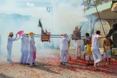 Phang Nga, Thailand - October 15, 2018: Group of men in white dress holding palanquin with Chinese god statue inside marching on stock photos