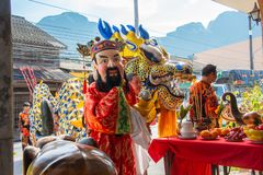 Phang Nga, Thailand - October 15, 2018: Man in Chinese costume with God mask together with dragon blessing people who pay respect royalty free stock photo