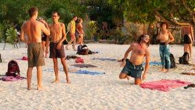 Phangan, Таиланд - пляж дзэна 23-ье февраля 2019 Молодые люди делают йогу acro на песке тренировки силы outdoors собирательно сток-видео