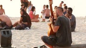 Phangan, Tailândia - 23 de fevereiro de 2019 Zen Beach O indivíduo novo de sorriso joga a guitarra em uma costa tropical do verão video estoque